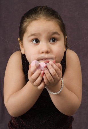 Child Holding Heart Pieces stock photo, Closeup view of a young girl holding heart shaped pieces by Richard Nelson