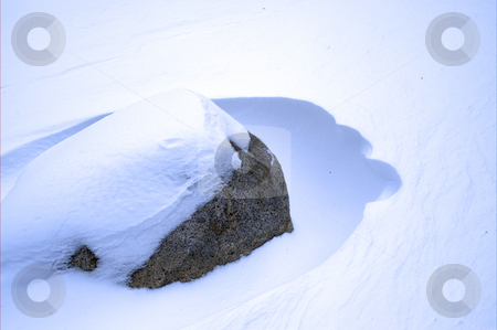 Rock And Snowdrift stock photo, A large boulder partially buried in a snowdrift by Lynn Bendickson