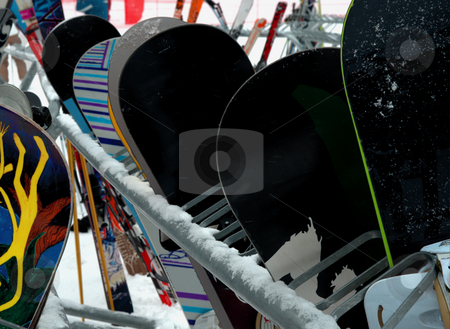 Snowboards stock photo, Many snowboards lined against a rack outside in the snow at a California ski resort. by Lynn Bendickson