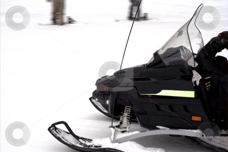 Black Snowmobile stock photo, A black snowmobile speeding across open snow by Lynn Bendickson