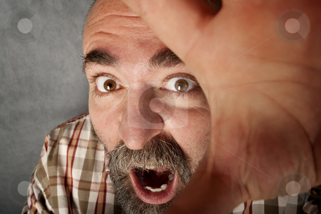 Closeup of man in his 40s screaming stock photo, Closeup of man in his forties with mustache screaming and fending off the camera by Scott Griessel