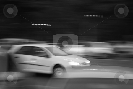Rapid escape stock photo, Small white car escaping fast through heavy traffic by Marius Blajut
