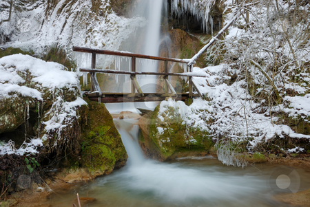 Bridge with Waterfall in Winter stock photo, Waterfall with icicles and snow around with a small wooden bridge on a winter day. by Denis Radovanovic