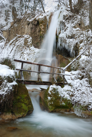 Winter Waterfall stock photo, Waterfall with icicles and snow around with a small wooden bridge on a winter day. by Denis Radovanovic