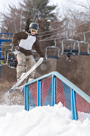 Grinding the Rail stock photo, A young man performs a rail slide on skis. Slight motion blur. by Todd Arena