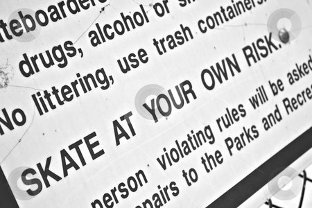 Skate Park Rules stock photo, A sign at the skate park clearly states that you will skate at your own risk.  Shallow depth of field. by Todd Arena