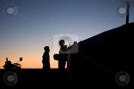 East and West encounter at dusk stock photo, The shadows of two boys exchanging a ball at dusk  in front of a ger in the Mongolian steppe by Marius Blajut