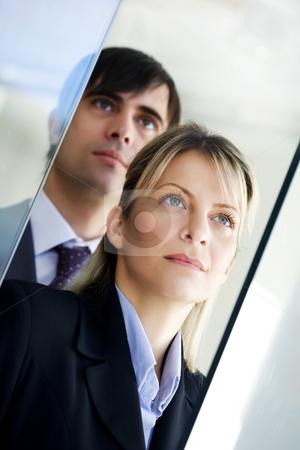 Business vision stock photo, Young ambitious businesspeople coming through a glass door by Liv Friis-Larsen