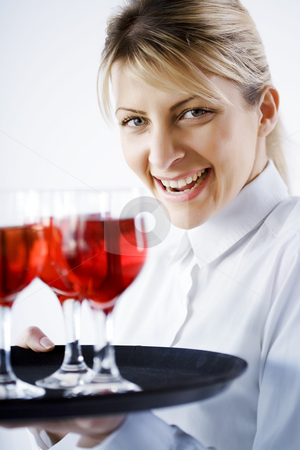 Smiling waitress stock photo, Happy smiling waitress serving red wine by Liv Friis-Larsen