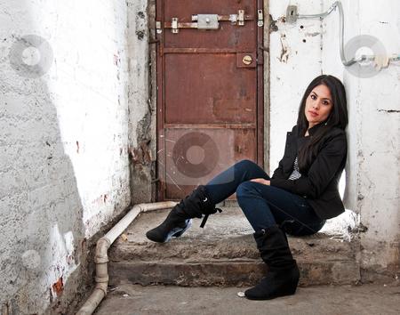 Girl sitting in basement stock photo, Beautiful Caucasian girl sitting on concrete floor in basement in front of brown door by Paul Hakimata