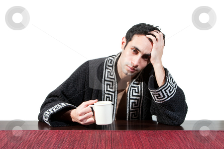 Morning guy drinking coffee stock photo, Handsome guy in the morning who just woke up sitting at a table in his robe with a cup recovering from his hangover, isolated on white by Paul Hakimata
