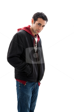 Mischievous guy stock photo, Cool handsome mischievous male wearing a red hoodie, black coat and jeans, with hands in pocket and head down, isolated by Paul Hakimata