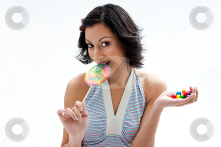 Candy girl stock photo, Happy beautiful candy girl with a hand full of colorful bubblegum candy balls licking a lollipop, isolated by Paul Hakimata