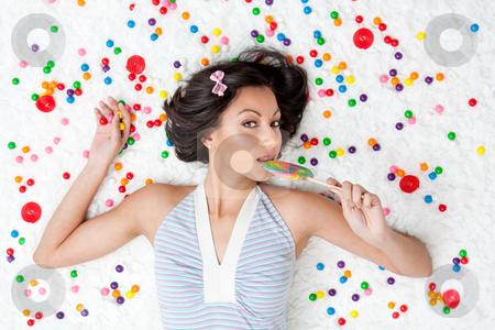 Lollipop girl stock photo, Young Latina woman laying on ruffled cloud like floor between colorful bubblegum balls eating a lollipop by Paul Hakimata