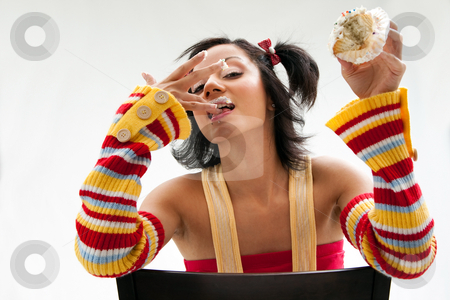 Cupcake girl stock photo, Beautiful Latina girl eating a cupcake licking her fingers and her icing covered lip, isolated by Paul Hakimata
