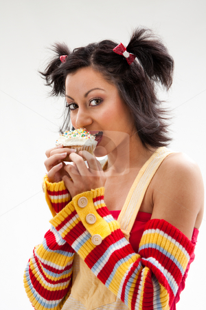 Cupcake girl stock photo, Beautiful Latina girl with huge eyes open holding a cupcake and biting it, isolated by Paul Hakimata