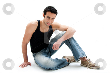 Handsome guy sitting on floor stock photo, Handsome Caucasian guy wearing black tank top and jeans sitting on floor looking down, isolated by Paul Hakimata