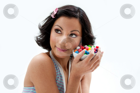 Happy candy girl stock photo, Happy beautiful candy girl with a bowl of colorful bubblegum candy balls next to her cheek, isolated by Paul Hakimata