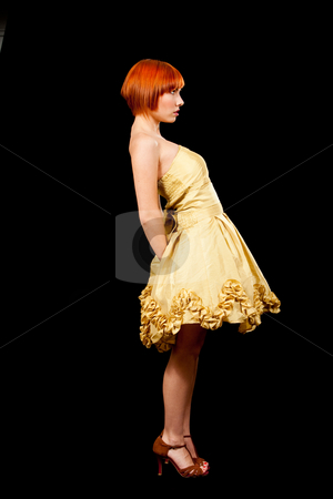 Redhead in yellow dress stock photo, Side profile of a beautiful Caucasian redhead woman in yellow cocktail dress standing leaning backward, isolated by Paul Hakimata