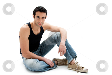 Handsome guy sitting on floor stock photo, Handsome Caucasian guy wearing black tank top and jeans sitting on floor, isolated by Paul Hakimata