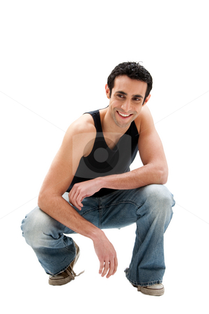 Handsome guy squatting stock photo, Handsome smiling Caucasian guy wearing black tank top and jeans squatting, isolated by Paul Hakimata