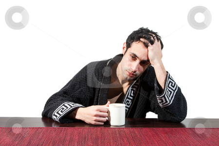Morning guy drinking coffee stock photo, Handsome stressed guy in the morning who just woke up sitting at a table in his robe with a cup and hand in his hair, isolated on white by Paul Hakimata