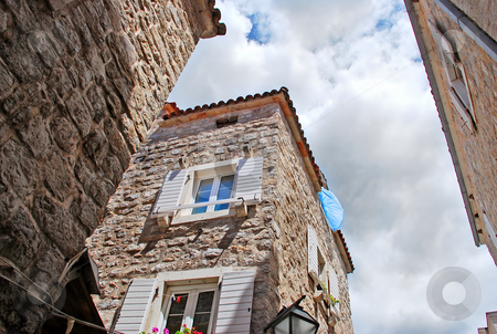 Blue curtain on wind stock photo, Old stone house exterior in Montenegro - Budva by Julija Sapic
