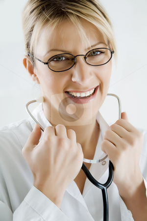Smiling female doctor stock photo, Young happy doctor, looking at the viewer by Liv Friis-Larsen