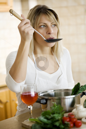 Tasting stock photo, Woman tasting the food she is cooking by Liv Friis-Larsen