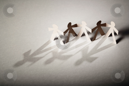 Paper Dolls stock photo, Line of cutout paper dolls throwing a shadow by Scott Griessel