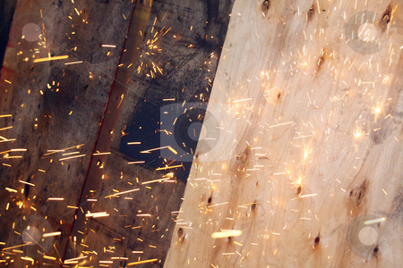 Sparks from a grinder stock photo, Sparks flying from a grinder, against wooden planels by Chris Alleaume