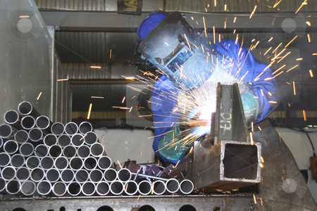 Artisan welding tubes in a production line stock photo, Artisan welding tubes in a production line by Chris Alleaume