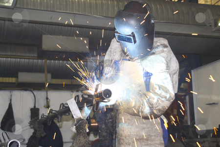 Factory worker concentrating on arc-welding stock photo, Factory worker concentrating on arc-welding by Chris Alleaume