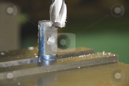 Drill press on metail piece stock photo, Closeup of industrial drill press by Chris Alleaume