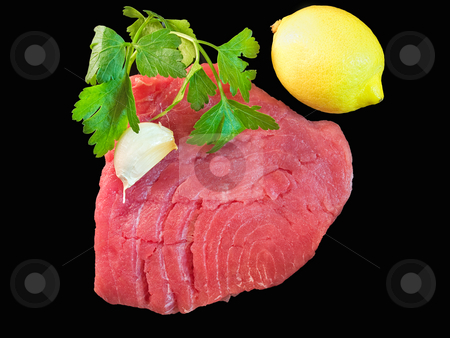 Tuna steak stock photo, Fresh tuna steak with  spices isolated on a black background. by Sinisa Botas