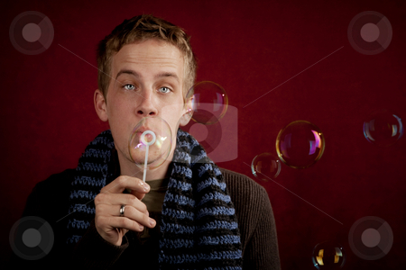 Young Man Blowing a Bubbles stock photo, Handsome young blonde man blowing a bubbles by Scott Griessel