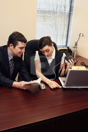 Digital Camera Setup - Confused Vertical stock photo, Businessman and businesswoman setting up a new digital camera. by Orange Line Media