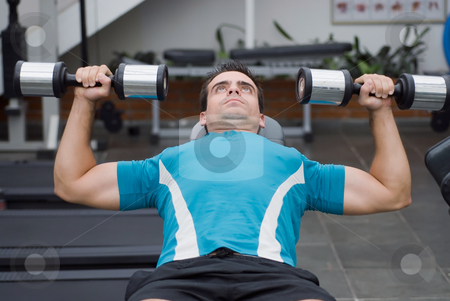 Dumbbell Bench Press stock photo, Male athlete doing a dumbbell bench press. by Orange Line Media