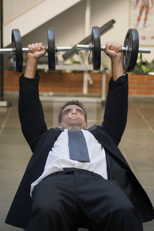 Preparing for a Meeting - Vertical stock photo, Vertically framed shot of an athletic, young businessman bench pressing weights in a gym by Orange Line Media