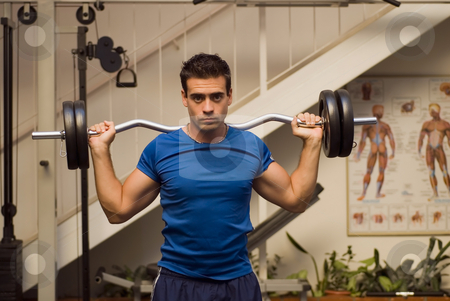 Man Doing Military Press stock photo, Male athlete resting a barbell on his back while standing in a gym by Orange Line Media