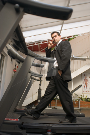 Businessman on Treadmill stock photo, Young, attractive businessman on a treadmill while talking on his cell phone by Orange Line Media