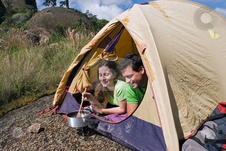 Couple Camping - Horizontal Shot stock photo, Horizontally framed shot of an attractive young couple cooking a meal in their tent. Shot is framed against a beautiful blue sky by Orange Line Media