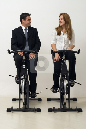 Business Team on Exercise Bikes - Vertical stock photo, Male and female business colleagues looking at each other while riding exercise bikes. Vertically framed - isolated shot. by Orange Line Media