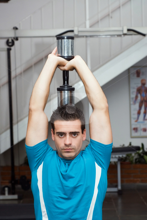 Tricep Extension stock photo, Male athlete excising his triceps with a dumbbell. by Orange Line Media