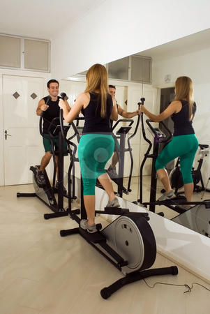 Couple Working Out stock photo, Attractive young couple working out on elliptical trainers at the gym. Facing each other. by Orange Line Media