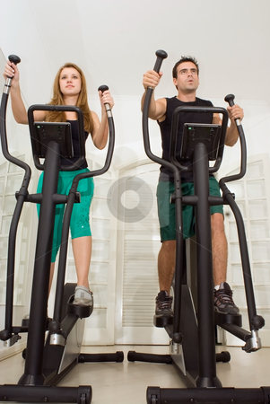 Couple Working Out stock photo, Attractive young couple working out on elliptical trainers at the gym. Facing the same direction by Orange Line Media