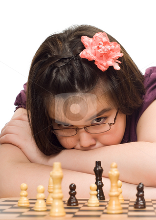 Child Playing Chess stock photo, A young girl thinking about her next move in a game of chess by Richard Nelson