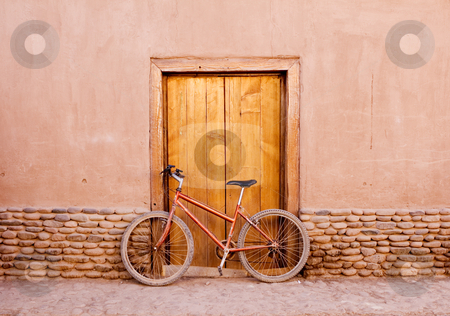 Desert bike stock photo, Bike sitting against the wooden door covered in dust by Audrey Amelie Rudolf