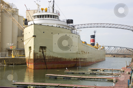 Boat at anchor stock photo, Rusty old hull achored at port taking on freight by Jonathan Hull