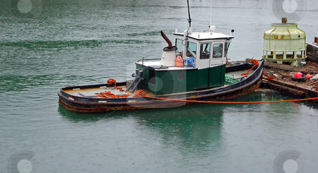 Green Tug Boat Tied to Dock stock photo, A green tug boat is tied to a dock in the rain. by Valerie Garner